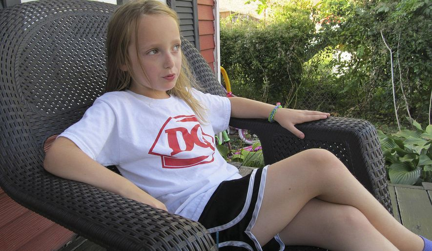 ADVANCE FOR USE SUNDAY, NOV. 20, 2016 AND THEREAFTER - In this Oct. 17,  2016 photo, Ava Jones, 8, matter-of-factly discusses the pain that comes with arthritis as she relaxes on the front porch of he rhome in Metamora, Ill. Ava has juvenile rheumatoid (idiopathic) arthritis. (Paul Swiech /The Pantagraph via AP)