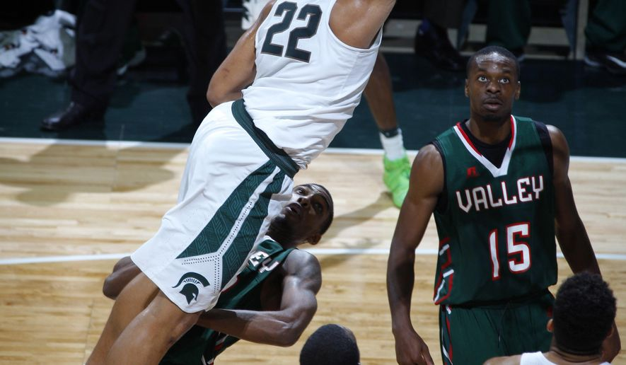 Michigan State's Miles Bridges (22) dunks over Mississippi Valley State's Jamal Watson, left, Ronald Strother (2) and Hasaan Buggs (15) during the first half of an NCAA college basketball game, Friday, Nov. 18, 2016, in East Lansing, Mich. (AP Photo/Al Goldis)