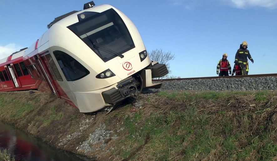 In this frame grab taken from video, emergency services attend the scene of a train derailment, near Winsum, Northern Netherlands, Friday, Nov. 18, 2016. A train derailed Friday in the northern Netherlands after colliding with a milk truck, injuring several passengers, emergency services said. Video footage and photos from the scene showed the front carriage of the train off the rails and leaning over a water-filled drainage ditch next to the track. The footage showed firefighters using a ladder to get across the ditch and into the train. (Persbureau Meter via AP)