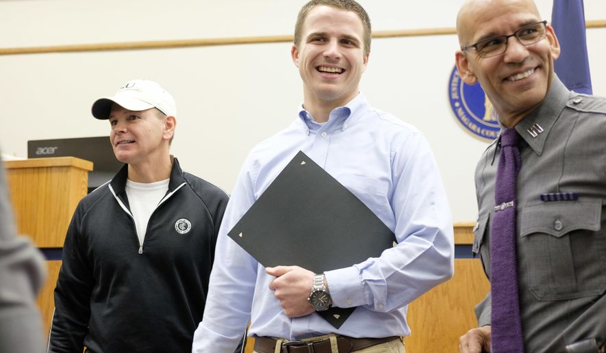 From left, Patrick Ellinger, Daniel Bronson and New York State Police Captain Eric Laughton laugh after Ellinger and Bronson were presented awards for helping to apprehend a suspect in a purse snatching in Lockport, N.Y., Friday, Nov. 18, 2016. Bronson, a University of Rochester quarterback, chased and tackled Biles after the man allegedly snatched a purse out of an elderly woman's hands. (Joed Viera/Lockport Union-Sun & Journal via AP)