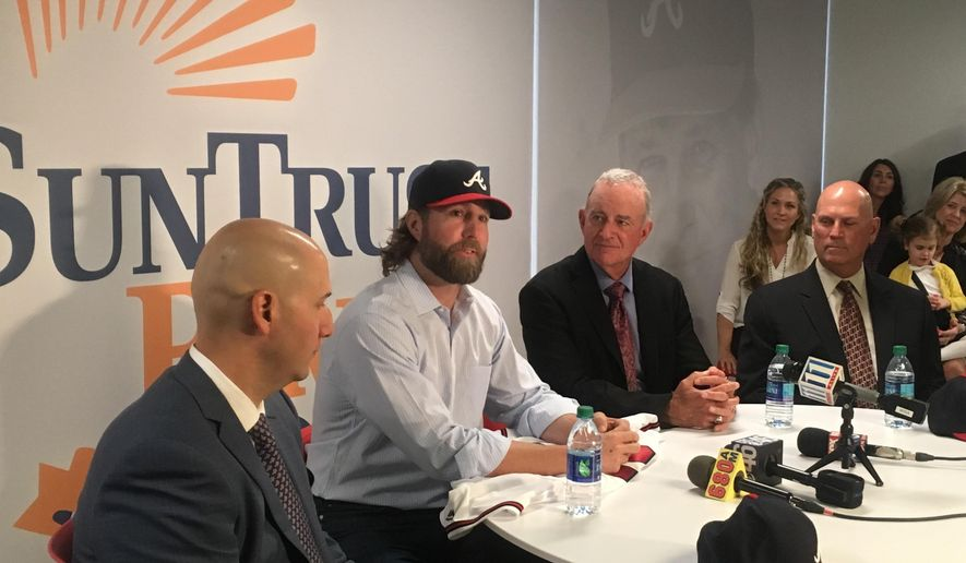 New Atlanta Braves baseball pitcher R.A. Dickey wears a Braves hat flanked by team general manager John Coppolella, left, and team president John Hart during an introductory press conference in Atlanta, Friday, Nov. 18, 2016. (AP Photo/Paul Newberry)