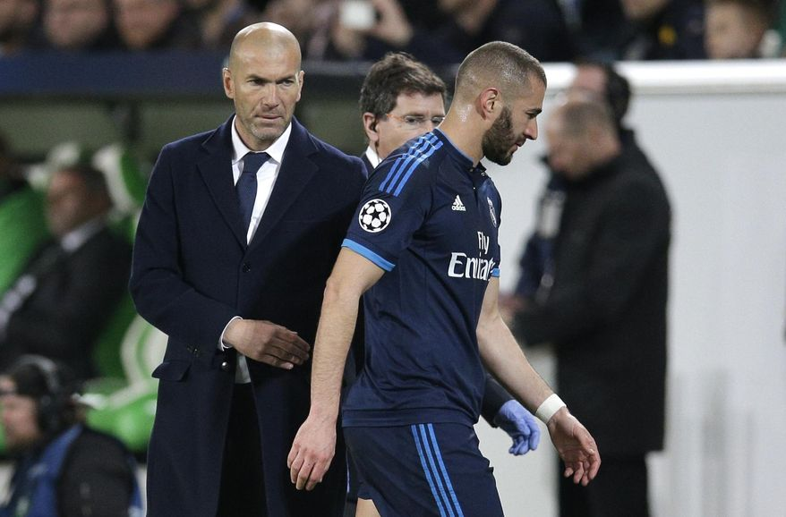 FILE - This is a Wednesday, April 6, 2016 file photo of Real Madrid's head coach Zinedine Zidane, left, as he looks on as Real Madrid's Karim Benzema leaves the pitch after suffering an injury during the Champions League first leg quarterfinal soccer match between VfL Wolfsburg and Real Madrid in Wolfsburg, Germany. Real Madrid coach Zinedine Zidane says Karim Benzema is available for the Madrid derby at Atletico on Saturday Nov. 19, 2016. (AP Photo/Michael Sohn, File)
