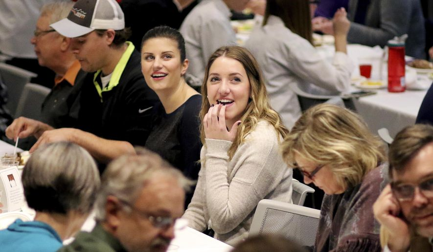 University of Wisconsin-Stout sophomore Kelly Ellwanger, right, and senior Cortney Woodis, watch a photo slideshow of their friend, Hussain Alnahdi at a memorial dinner held in his honor on Thursday, Nov. 17, 2016, in Menomonie, Wis. Alnahdi, 24, from Saudi Arabia, was fatally assaulted Halloween weekend in downtown Menomonie. (Marisa Wojcik/The Eau Claire Leader-Telegram via AP)