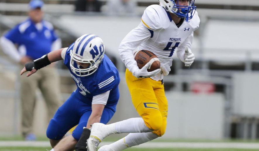 Catholic Memorial's Max Cooper (4) runs against Green Bay Notre Dame's Quinn Snyder during the first half of the WIAA Division 3 high school football championship game Friday, Nov. 18, 2016, in Madison, Wis. (AP Photo/Andy Manis)