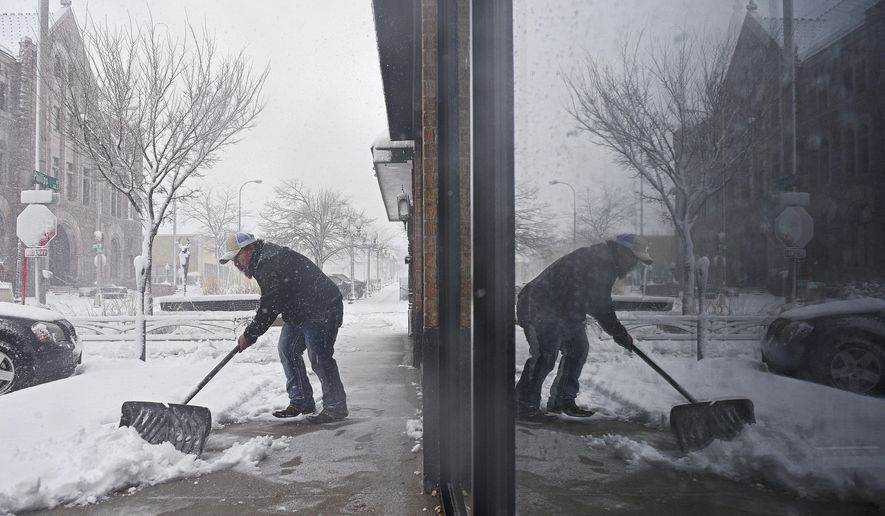 Philip Peter shovels snow in front of the restaurant during a snow storm, Friday, Nov. 18, 2016, in Sioux Falls, S.D.   The National Weather Service has issued a blizzard warning for Friday in eastern parts of North and South Dakota and Minnesota, as well as winter storm warnings for other parts of those states and Nebraska.     (Joe Ahlquist/The Argus Leader via AP)
