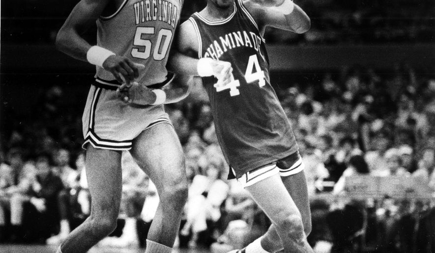 FILE - In this Dec. 23, 1982, file photo, Chaminade's Tony Randolph, right, moves around Virginia's Ralph Sampson during an NCAA college basketball game in Honolulu. Chaminade's 77-72 victory over Ralph Sampson and top-ranked Virginia is widely considered the biggest upset in college basketball, among the greatest in any sport. Unlike today's world of 24-hour sports networks, social media and smartphones, the game was played in relative obscurity. (AP Photo/File)