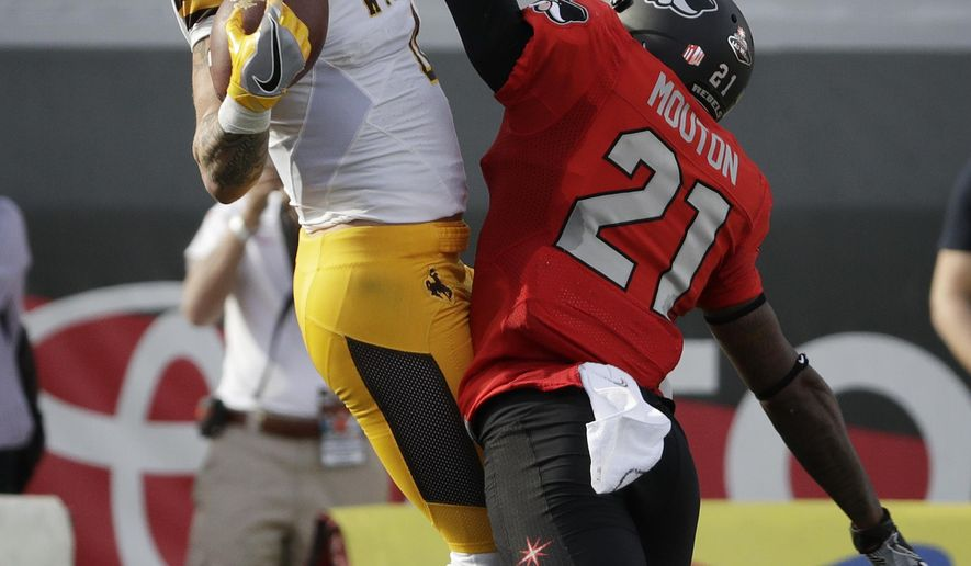 Wyoming wide receiver Tanner Gentry catches a pass over UNLV defensive back Darius Mouton before Gentry scored a touchdown during the first half of an NCAA college football game, Saturday, Nov. 12, 2016, in Las Vegas. (AP Photo/John Locher)