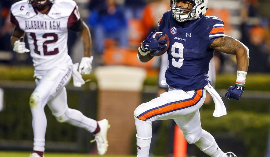 Auburn running back Kam Martin (9) carries the ball in for a touchdown past Alabama A&M defensive back Devonte Simon (12) during the second half of an NCAA college football game Saturday, Nov. 19, 2016, in Auburn, Ala. (AP Photo/Butch Dill)