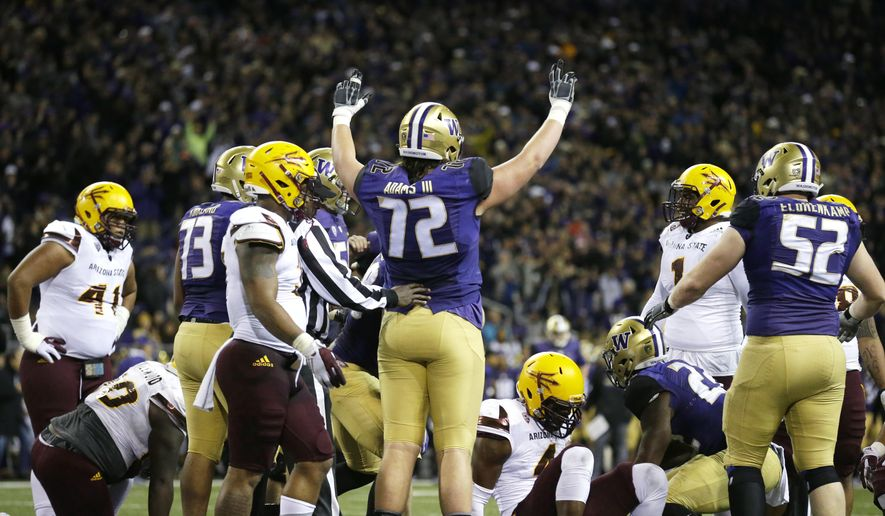 Washington offensive lineman Trey Adams (72) signals a touchdown scored by Washington running back Lavon Coleman, second from lower right, in the first half of an NCAA college football game against Arizona State, Saturday, Nov. 19, 2016, in Seattle. (AP Photo/Ted S. Warren)