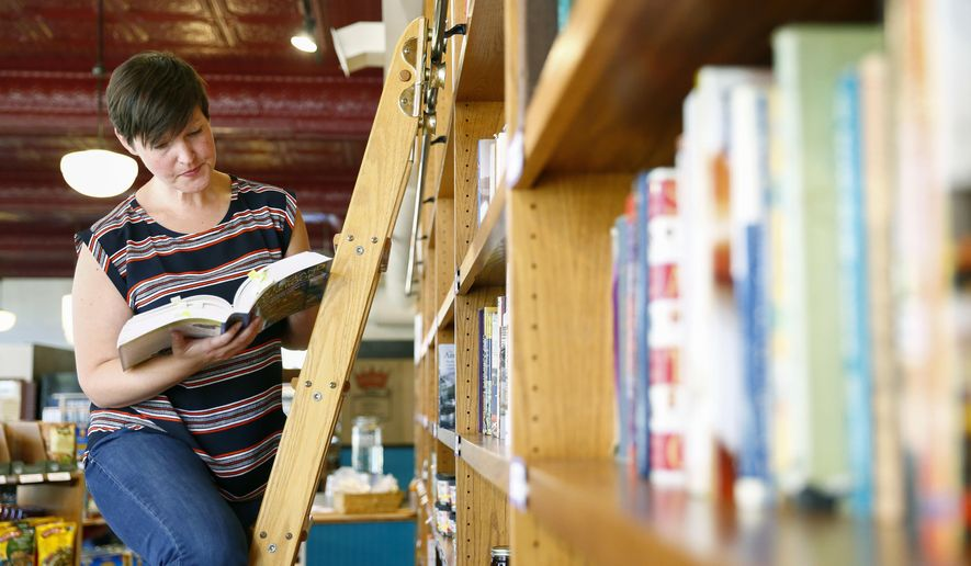 ADVANCE FOR SATURDAY, NOV. 19, 2016 -  In this Oct. 27, 2016 photo, Dania Fiorito looks at one of her father's 3,000 cookbooks that currently are on display at The Farmer's Pantry, in Greeley, Colo. The community is welcome to check out a book, from the Fiorito collection, for free. (Alyson McClaran  /The Greeley Tribune via AP)