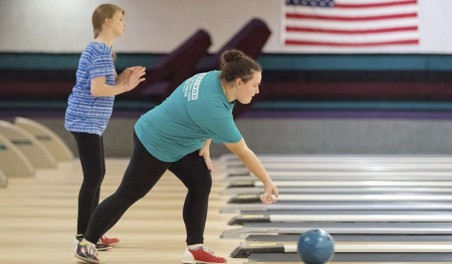 ADVANCE FOR USE SATURDAY, NOV. 19 - In this Tuesday, Nov. 1, 2016 photo, Omaha North senior Ciera Pieters, right, rolls while Hannah Faber watches her ball in Omaha, Neb. It's the first season for North High and more than 40 other high school unified bowling teams across the state.(Matt Miller/Omaha World-Herald via AP)