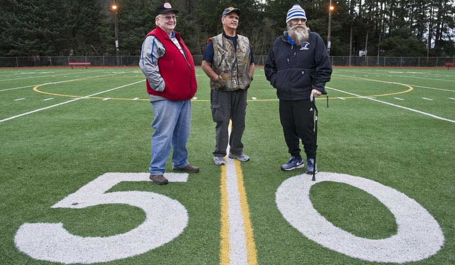 In this Wednesday, Nov. 9, 2016 photo, Jeep Rice, left, Ray Bradley, center, and Tom Ramage, who are retiring from coaching football, ppse for a photo at Adair-Kennedy Memorial Park In Juneau, Alaska. The three have coached for the Juneau Youth Football League, Juneau-Douglas High School and Thunder Mountain High School. (Michael Penn  /The Juneau Empire via AP)