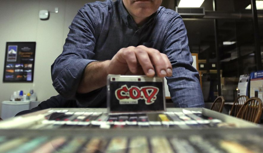 Pacey Foster, a rap historian and professor at UMass, holds up a recording of the musical group COD as he poses with a collection of hip-hop cassette tapes from the 1980's at the Boston campus of the University of Massachusetts in Boston, Thursday, Nov. 17, 2016. Thanks to UMass, the world will soon have access to 300 unreleased demo tapes from the early days of Boston hip-hop. The university paired with Boston Public Library to form a new hip-hop archive that's the latest example of colleges treating hip-hop as a scholarly subject. (AP Photo/Charles Krupa)