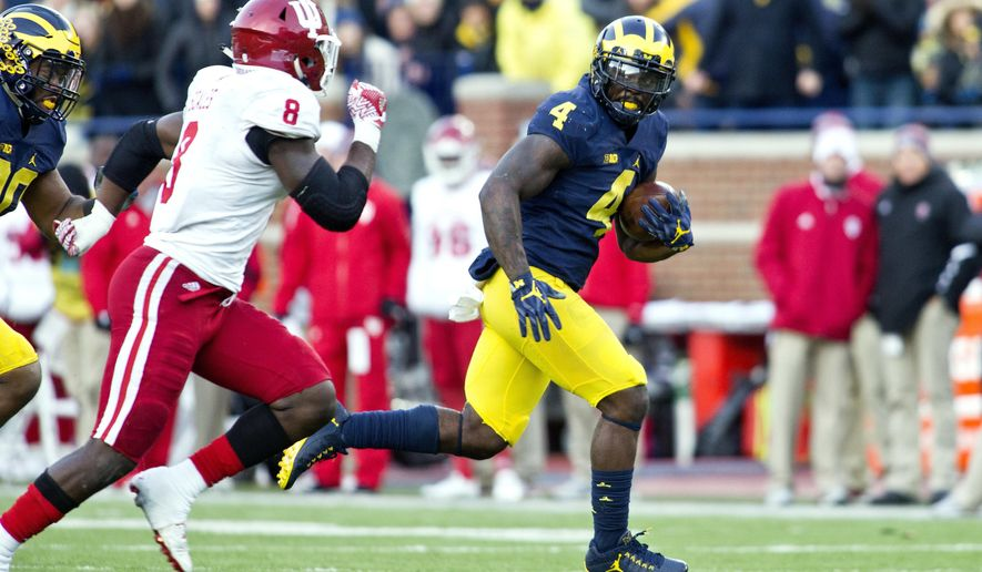 Michigan running back De'Veon Smith (4) rushes ahead of Indiana linebacker Tegray Scales (8) in the second quarter of an NCAA college football game in Ann Arbor, Mich., Saturday, Nov. 19, 2016. (AP Photo/Tony Ding)