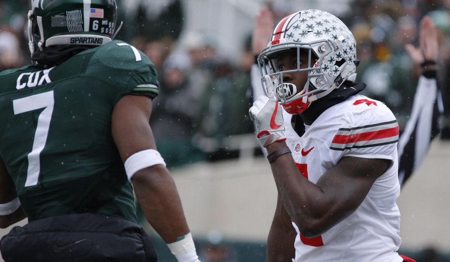 Ohio State's Curtis Samuel, right, celebrates his 24-yard touchdown reception in front of Michigan State's Demetrious Cox during the first quarter half of an NCAA college football game, Saturday, Nov. 19, 2016, in East Lansing, Mich. (AP Photo/Al Goldis)