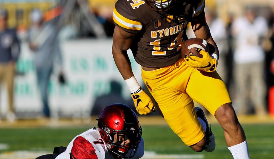 Wyoming wide receiver C.J. Johnson runs down the field after avoiding a tackle from San Diego State safety Kameron Kelly during the first half of an NCAA college football game in Laramie, Wyo., Saturday, Nov. 19, 2016. (AP Photo/Shannon Broderick)