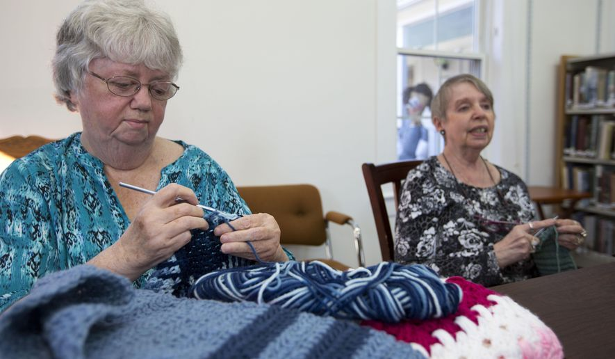 In this photo taken Friday, Nov. 4, 2016, Pat Clement, left, and Christine Hrycuna work on knitting scarves at the Griffin Free Public Library in Auburn, N.H. The two are part of a group that knit around 400 scarves this year and hung them on a park fence for anyone to grab and keep. (AP Photo/Jim Cole)