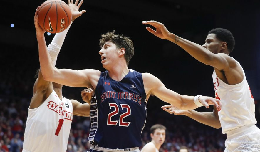 St. Mary's Dane Pineau (22) catches a pass against Dayton's Darrell Davis (1) and forward Xeyrius Williams (20) in the first half an NCAA college basketball game, Saturday, Nov. 19, 2016, in Dayton, Ohio. (AP Photo/John Minchillo)