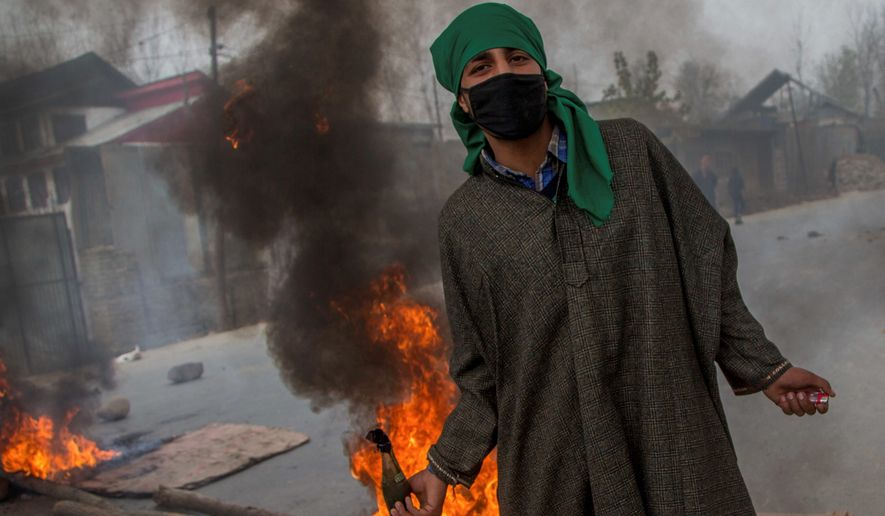 A Kashmiri villager prepares to throw a Molotov cocktail at Indian police during a protest on Sunday. (Associated Press)