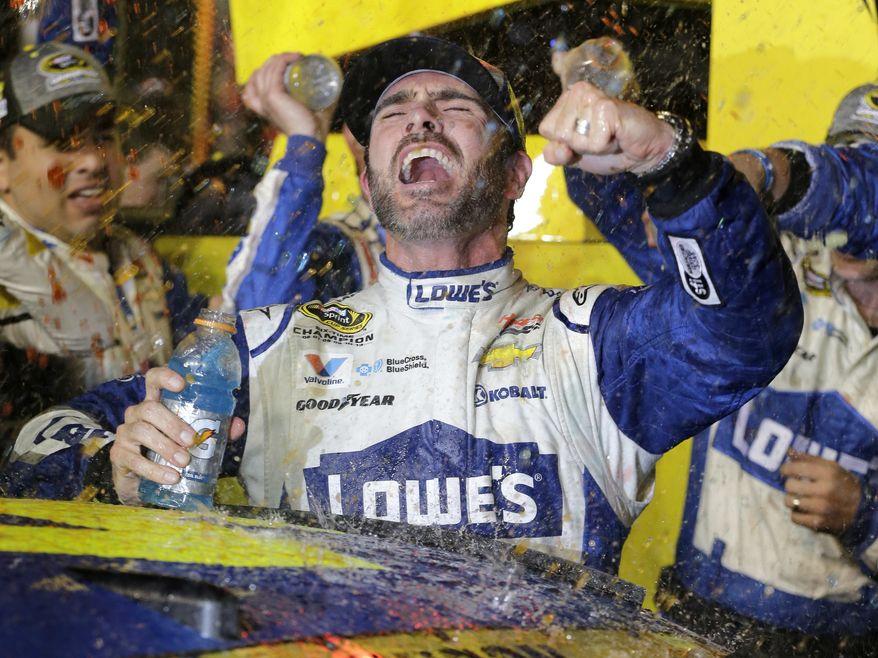 Jimmie Johnson celebrates his NASCAR Sprint Cup auto race and season title win Sunday, Nov. 20, 2016, in Homestead, Fla. (AP Photo/Terry Renna)