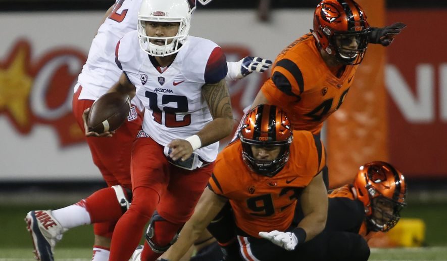 Arizona quarterback Anu Solomon (12) gets away from the Oregon State pass rush during the first half of an NCAA college football game in Corvallis, Ore., Saturday Nov. 19, 2016. (AP Photo/Timothy J. Gonzalez)