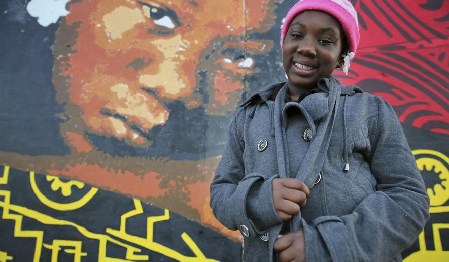 In this Sept. 25, 2016 photo, Jariah Edmond, 9, stands next to her likeness on the mural created by Brazilian artist Ananda Nahu at Lakeview Terrace Estates, in Cleveland. Edmond is one of a handful of Lakeview residents who's portraits adorn the mural. A wall that has long isolated one of the country's oldest low-income housing projects from the rest of a Cleveland neighborhood has been covered with a colorful mural of local children as part of an artistic effort to brighten the area. (Gus Chan/The Plain Dealer via AP)