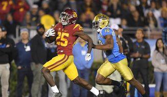 Southern California running back Ronald Jones II, left, runs 60 yards for a touchdown as UCLA defensive back Fabian Moreau runs behind during the first half of an NCAA college football game Saturday, Nov. 19, 2016, in Pasadena, Calif. (AP Photo/Mark J. Terrill)