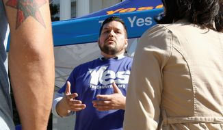 FILE - In this Nov. 9, 2016 file photo, Marcus Ruiz Evans, center, of The Yes California Independence Campaign, talks to passersby about California succeeding from the United States and becoming its own nation in Sacramento, Calif. A group calling for California to secede from the United States submitted a proposed petition Monday, Nov. 21, 2016, seeking a ballot measure that would strip the state constitution of language that says California is an inseparable part of the nation. The Yes California Independence Campaign hopes to put a question on the November 2018 ballot authorizing a vote on independence in spring 2019. (AP Photo/Rich Pedroncelli, File)
