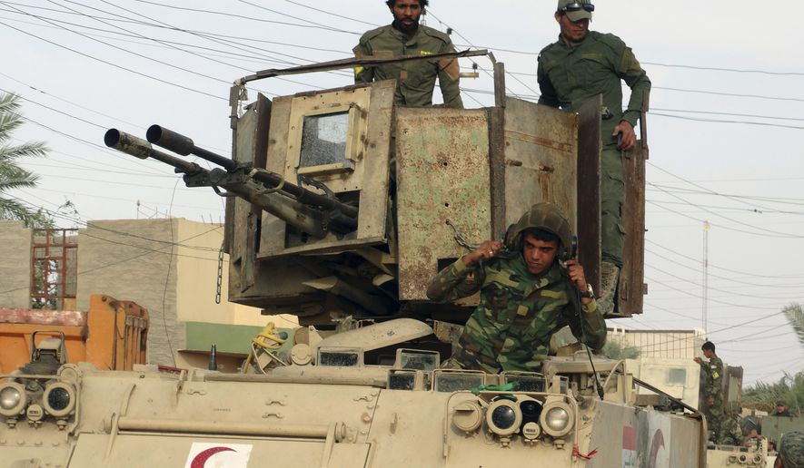 Iraqi Shiite Hezbollah Brigade militiamen prepare their armored vehicles for fighting against the Islamic State east of Ramadi, Iraq, in this In this May 27, 2015, file photo. (Associated Press) ** FILE **