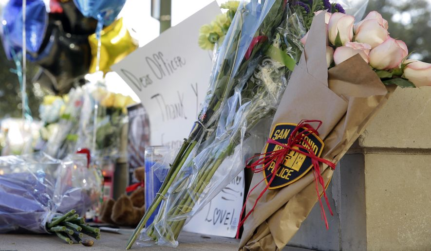 Flowers, balloons and notes are placed at a makeshift memorial on Monday for slain San Antonio Police Det. Benjamin Marconi, a 20-year veteran of the force. Marconi was fatally shot during a traffic stop near police headquarters Sunday. (Associated Press)
