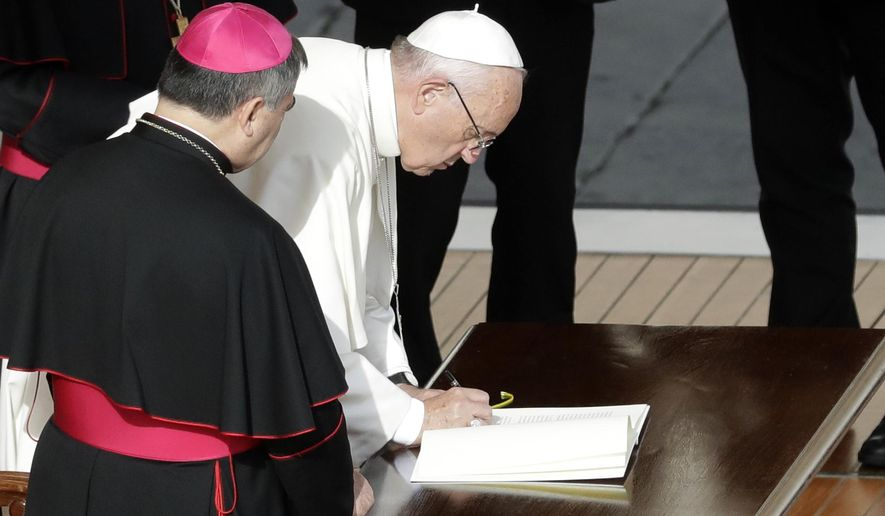 Pope Francis signs a letter at the end of a Mass on the occasion of the closing of the Holy Door of St. Peter's Basilica at the Vatican, Sunday, Nov. 20, 2016. The Vatican said the letter, addressed to all the church,  expressed the pope's intention that the church can continue to live out the mercy with the same intensity felt during the entire special Jubilee Holy Year.  (AP Photo/Gregorio Borgia)