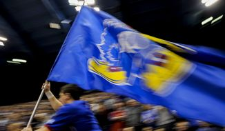 A University of Kansas cheerleader leads the team out on the court before their game NCAA college basketball against the Kansas State Wildcats game Wednesday, Feb. 3, 2016, in Lawrence, Kan. Kansas  beat K-State, 77-59. (AP Photo/Reed Hoffmann) ** FILE **