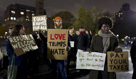 In this Tuesday, Nov. 15, 2016 photo, protestors hold banners during a protest against President-elect Donald Trump in Washington Square Park in New York. (AP Photo/Muhammed Muheisen)