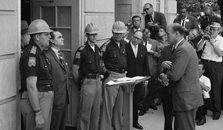 Attempting to block integration at the University of Alabama, Governor George Wallace stands defiantly at the door while being confronted by Deputy U.S. Attorney General Nicholas Katzenbach. (Wikipedia)