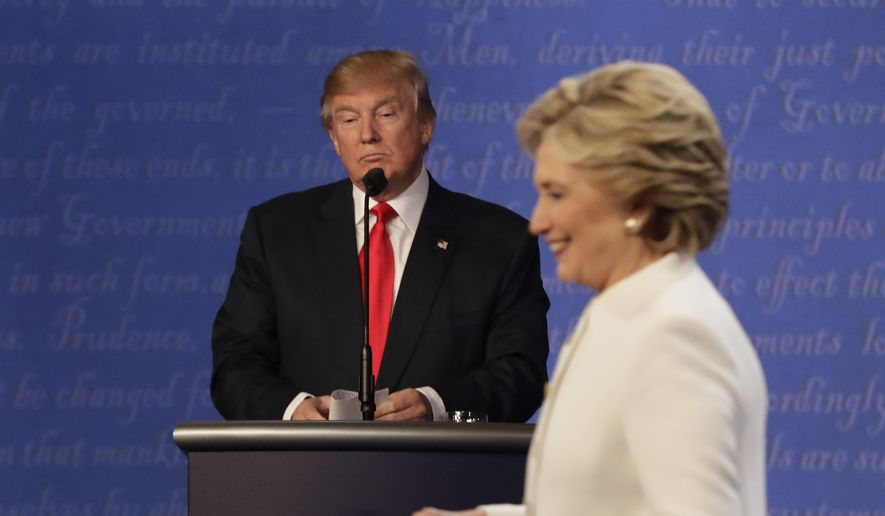 In this Oct. 19, 2016, file photo, Republican presidential nominee Donald Trump waits behind his podium as Democratic presidential nominee Hillary Clinton makes her way off the stage following the third presidential debate at UNLV in Las Vegas. (AP Photo/David Goldman) ** FILE **