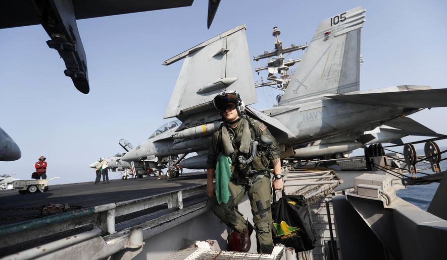 In this Tuesday, Nov. 22, 2016 photo, Lt. Jennifer Sandifer, a 27-year old fighter pilot from Austin, Texas, walks towards F/A-18E Super Hornet jet before launching from the deck of the U.S.S. Dwight D. Eisenhower aircraft carrier towards targets in Iraq and Syria. Like on a typical day of operations, Sandifer, a wingman in the carrier's Gunslingers squadron, will spend Thanksgiving flying 6-9 hours to strike or scout targets identified by anti-IS coalition ground forces on the ground around Mosul, Raqqa and others sites. (AP Photo/Petr David Josek)