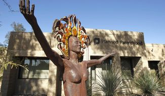 FILE - In this Jan. 23, 2011 file photo, a statue representing women's empowerment stands in front of a Planned Parenthood facility in Tucson, Ariz. The number and rate of abortions tallied by federal authorities have fallen to their lowest level in decades, according to new data released Wednesday, Nov. 23, 2016.   (AP Photo/Ross D. Franklin, File)