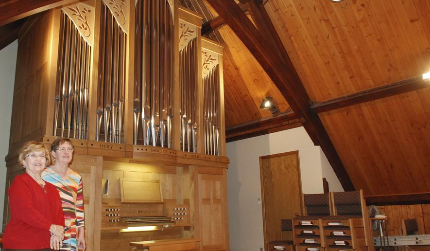 In this Nov. 14, 2016 photo, Cyndi Lauritsen, chairman of the organ committee, left, and organist Claire Bushong stand in front of the new mechanical action pipe organ at Sinai Lutheran Church in Fremont, Neb. Lauritsen spent many hours working to get just the right pipe organ for the Fremont church.  Now, church members look forward to Sunday services and future concerts, fulfilling a longtime dream for the church, which is celebrating its 125th anniversary.  (Tammy Real-McKeighan/Fremont Tribune via AP)