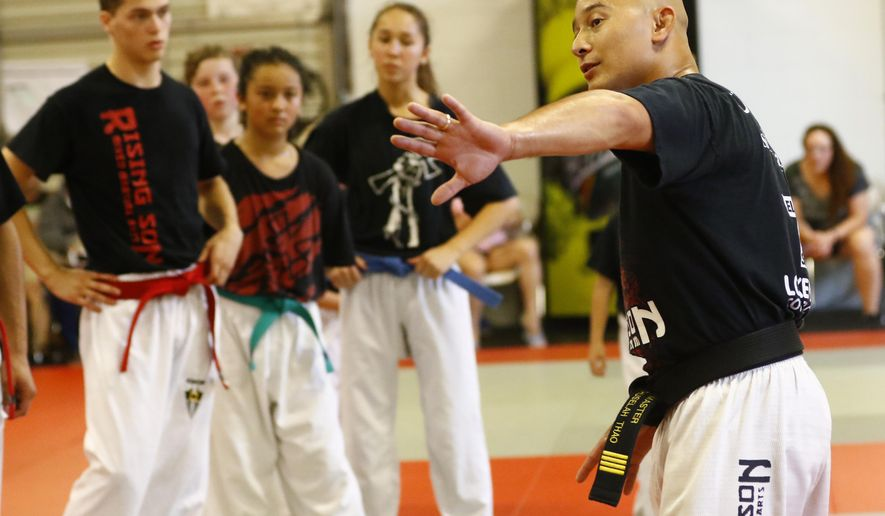 In this Aug. 4, 2016 photo, owner and instructor Lah Thao trains his martial art students at the Rising Son in Wausau, Wis. Thao uses martial arts to overcome bullying.  (T'xer Zhon Kha/The Post-Crescent via AP)