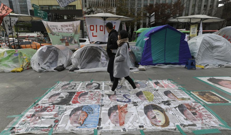 A couple walks on paintings criticizing South Korean President Park Geun-hye on a street in Seoul, South Korea, Wednesday, Nov. 23, 2016. Park's office on Wednesday confirmed revelations by an opposition lawmaker that it purchased about 360 erectile dysfunction Viagra pills and the generic version of the drug in December. (AP Photo/Ahn Young-joon)