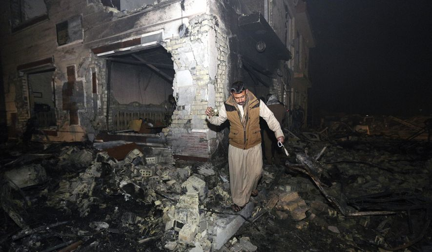 A civilian searches for survivors in the rubble at the scene of a car bomb attack near the city of Hilla about 95 kilometers (60 miles) south of Baghdad, Iraq, Thursday, Nov. 24, 2016. A car bomb tore through a gas station on Thursday, killing and wounding scores of people, including 20 Iranians Shiite pilgrims, in an attack claimed by the Islamic State group. (AP Photo/Hadi Mizban)