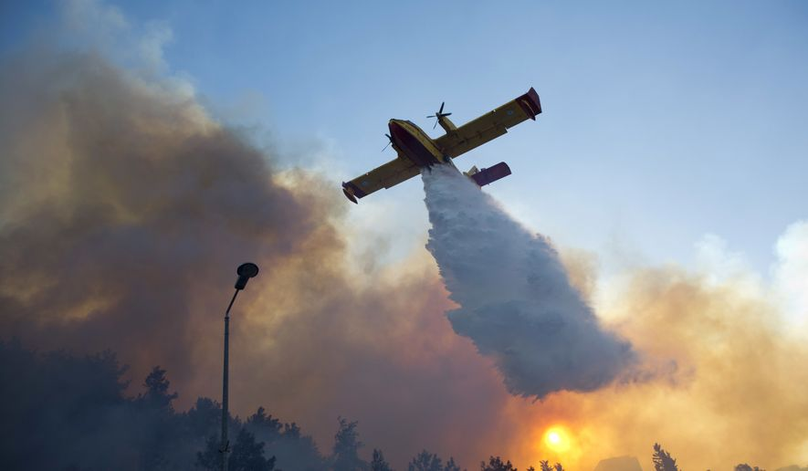 A firefighting plane from Greece fights a wildfire over Haifa, Israel, Thursday, Nov. 24, 2016. A raging wildfire ripped through parts of Israel's third-largest city on Thursday, forcing tens of thousands of people to evacuate their homes and prompting a rare call-up of hundreds of military reservists to join overstretched police and firefighters. Spreading quickly due to dry, windy weather, the fire quickly spread through Haifa's northern neighborhoods. While there were no serious injuries, several dozen people were hospitalized for smoke inhalation. (AP Photo/Ariel Schalit)