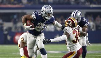 Dallas Cowboys running back Ezekiel Elliott (21) breaks a tackle-attempt by Washington Redskins safety Donte Whitner Sr. (39) with help from Cowboys receiver Vince Mayle (16) in the second half of an NFL football game, Thursday, Nov. 24, 2016, in Arlington, Texas. (AP Photo/Ron Jenkins)