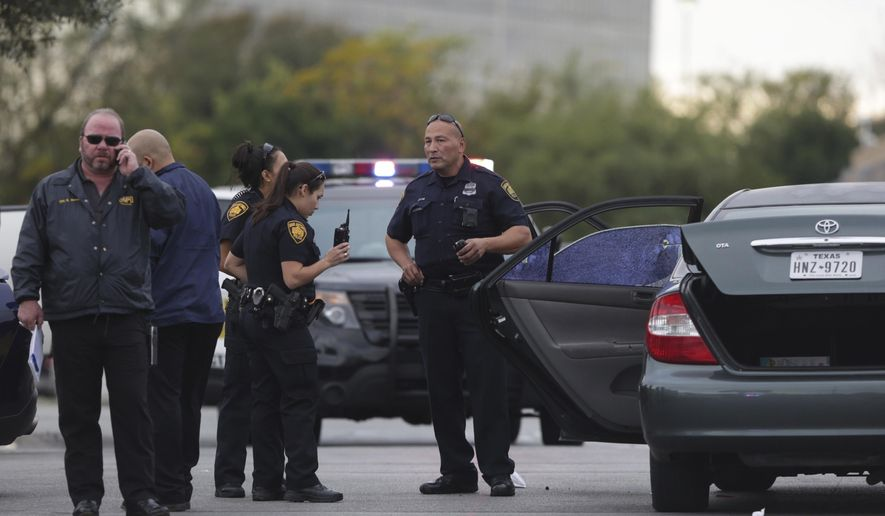San Antonio police investigate the scene of a shooting in the Wal-Mart parking lot in San Antonio, Friday, Nov. 25, 2016. A man has been killed and a woman critically wounded when police say the man tried to stop another man from beating a woman in the crowded San Antonio parking lot. The incident happened Friday afternoon outside of a Wal-Mart in northwestern San Antonio. (Bob Owen/The San Antonio Express-News via AP)
