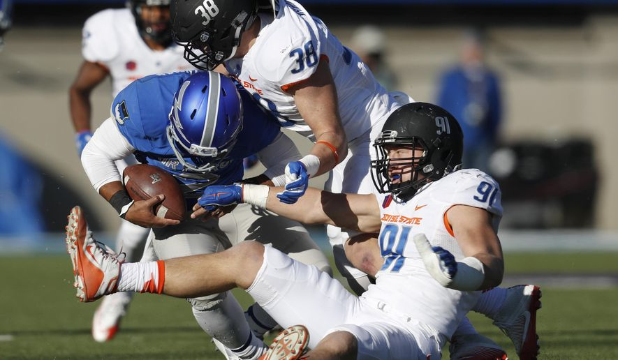 Air Force quarterback Arion Worthman, left, is stopped after a short gain by Boise State linebacker Leighton Vander Esch, back right, and defensive end Durrant Miles in the first half of an NCAA college football game Friday, Nov. 25, 2016, at Air Force Academy, Colo. (AP Photo/David Zalubowski)