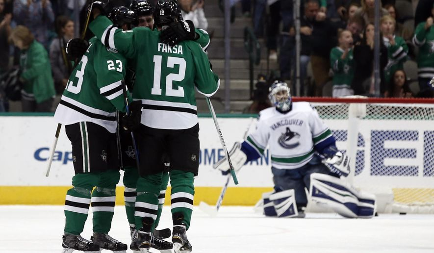 Dallas Stars' Esa Lindell (23), Jamie Oleksiak (5) and Radek Faksa (12) celebrate after Faksa scored against Vancouver Canucks goalie Ryan Miller (30) during the second period of an NHL hockey game, Friday, Nov. 25, 2016, in Dallas. (AP Photo/Mike Stone)