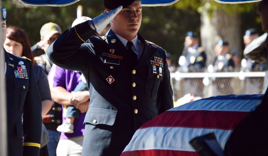 In this Nov. 19, 2016 photo, a member the the honor guard from Fort Polk salutes the casket of Sgt. James Martin in Anacoco, La. Martin was deployed to Korea in late November 1950 with the 3rd Battalion, 31st Infantry Regiment, 7th Infantry Division and was reported missing in action as of Dec. 3, 1950. In 2001, Martin's remains, as well as the remains of seven others, were uncovered during the 25th Joint Recovery Operation on the eastern bank of the Chosin Reservoir. He was identified fifteen years later when a DNA analysis matched two of his sisters. (Jordan Allen /The Daily Town Talk via AP)