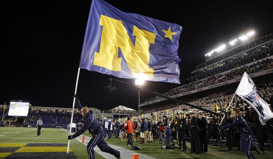 FILE - In this Nov. 14, 2015, file photo, a cheerleader carries a flag after a Navy touchdown in the second half of an NCAA college football game against SMU, in Annapolis, Md. While triple-option Navy has already clinched the West Division and a spot in the conference title game, the Midshipmen (8-2, 6-1 AAC, No. 25 CFP) still have a chance to host the Dec. 3 game depending on who wins the East. (AP Photo/Patrick Semansky, File)
