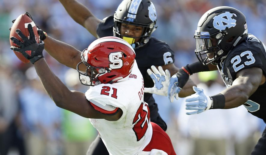 North Carolina State's Matthew Dayes (21) reaches out out for a touchdown as North Carolina's M.J. Stewart (6) and Cayson Collins (23) try to tackle during the first half of an NCAA college football game in Chapel Hill, N.C., Friday, Nov. 25, 2016. (AP Photo/Gerry Broome)