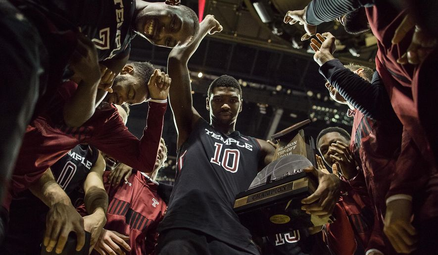 Temple's Mark Williams (10) holds the trophy as he celebrates the championship with teammates after an NCAA college basketball game against West Virginia in the NIT Season Tip-Off tournament in New York, Friday, Nov. 25, 2016. (AP Photo/Andres Kudacki)